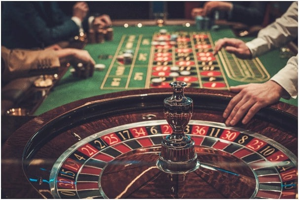 Dealers hand on edge of roulette wheel